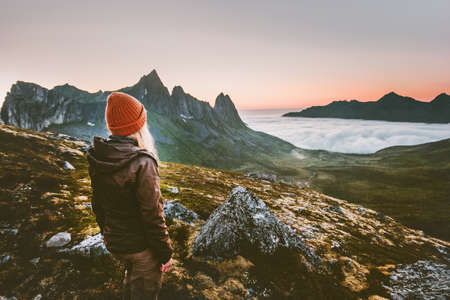 Woman tourist hiking survival in mountains alone outdoor active lifestyle travel adventure extreme vacations sunset Norway landscape Imagens