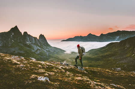Man backpacker hiking in mountains alone  outdoor active lifestyle travel adventure vacations sunset Norway landscape
