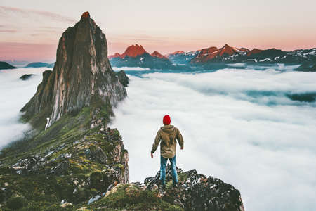 Traveler man on cliff alone enjoying sunset Segla mountain adventure outdoor in Norway hiking active vacations traveling lifestyle