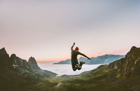 Jumping man in mountains vacations outdoor Travel Lifestyle adventure concept active success motivation and fun euphoria emotions