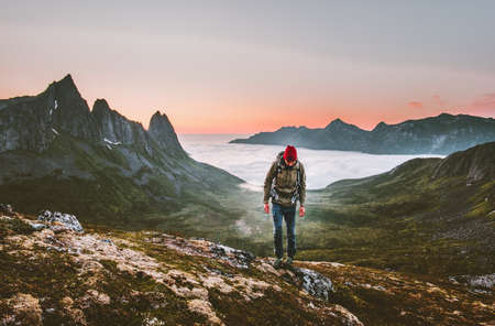 Man hiking survival in mountains alone outdoor active lifestyle travel adventure extreme vacations sunset Norway landscape