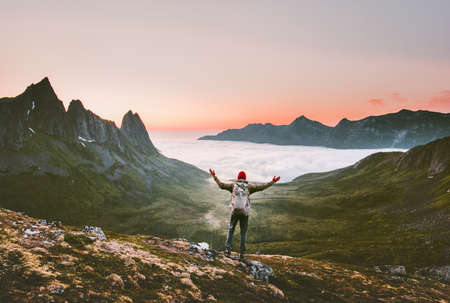 Tourist man with backpack hiking in mountains alone vacations outdoor active lifestyle travel adventure sunset Norway landscape Imagens