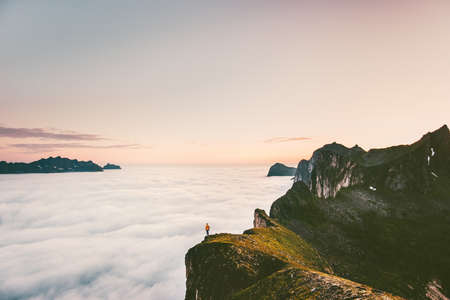 Traveler on the edge cliff mountain above sunset clouds travel adventure lifestyle  journey vacations tranquil landscape in Norway