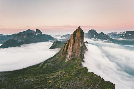 Segla Mountain rocky peak Landscape over clouds and fjord aerial view in Norway Travel destinations awesome scenery Senja islands