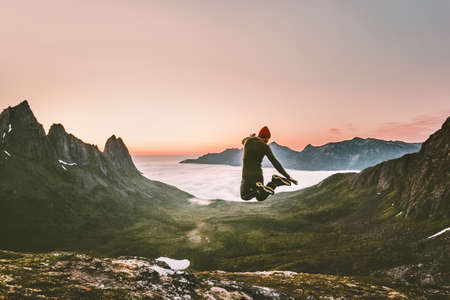 Happy man jumping outdoor Travel Lifestyle adventure concept active vacations in Norway sunset mountains success and fun euphoria emotions