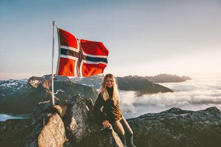 Woman and Norway flag on mountain summit blonde girl traveling enjoying view hiking adventure vacations outdoor active lifestyle