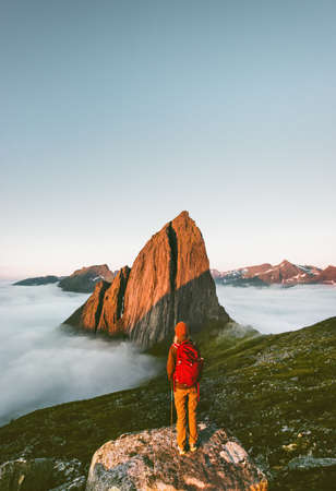Backpacker enjoying Segla mountain view traveling in Norway hiking adventure trip outdoor lifestyle alone active vacations sunset landscape Imagens