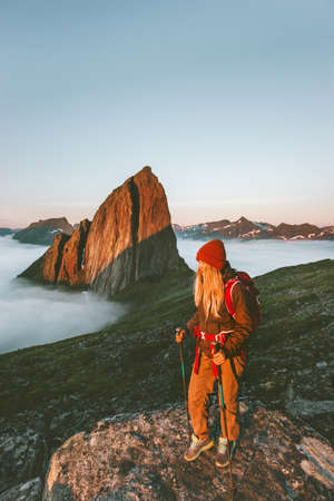 Woman traveler hiking outdoor in Norway active vacations traveling adventure lifestyle girl with backpack enjoying sunset Segla mountain