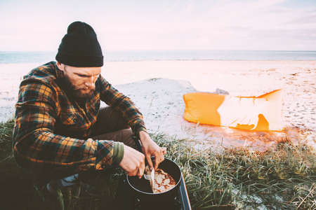Man cooking outdoor pancakes breakfast travel lifestyle vacations camping kitchen on beach weekend journey Foto de archivo