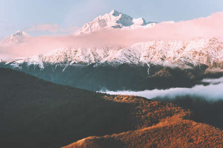 Sunset mountains with clouds landscape Travel aerial view wilderness nature snowy peak and forest tranquil evening scenery