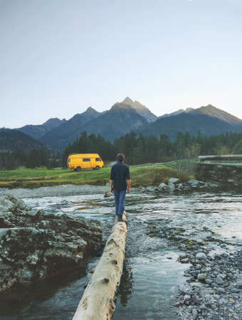 Man traveler with yellow van camping in mountains travel adventure healthy lifestyle summer vacations  Zdjęcie Seryjne