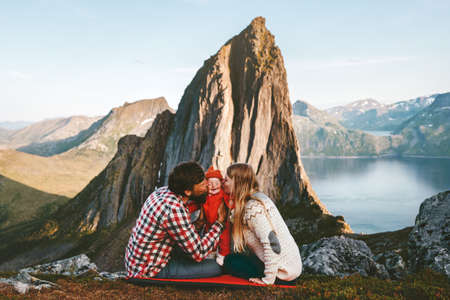 Happy family traveling hiking with baby adventure vacations outdoor mother and father kissing child parenthood lifestyle trip in Norway Stock Photo