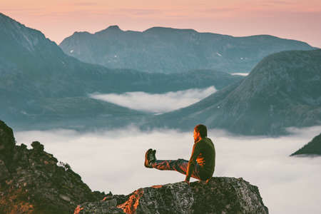 Man training sports on mountain cliff above clouds alone travel healthy lifestyle adventure journey outdoor vacations