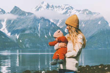 Mother traveling with child in Norway mountains family lifestyle mom holding infant baby vacations outdoor activity  Mothers day