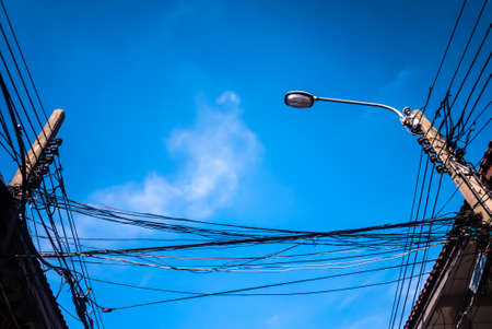 cable tangle: Electricity poles and street light complicated wiring on the pole under blue sky.