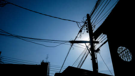 sunshines: Silhouette of electricity post and  wiring under blue sky. Stock Photo