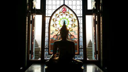 sunshines: Silhouette buddha statue has flower and sun pattern stained glass is background,  Wat Pramahathadchedipakdeeprakad  Prachuapkhirikhan Thailand, Historical place and Public place.