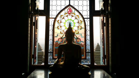 Silhouette buddha statue has flower and sun pattern stained glass is background,  Wat Pramahathadchedipakdeeprakad  Prachuapkhirikhan Thailand, Historical place and Public place.