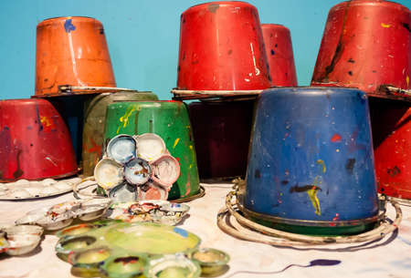 vibrant paintbrush: Art palettes and Paint buckets for an artist lays and mixes colors.