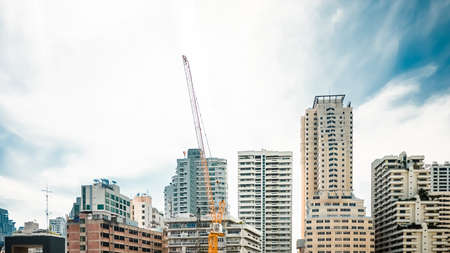 steel tower: Crane on under construction building among other buildings. Stock Photo