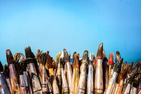 paintbrush: Row of artist paintbrushes closeup with blue wall background.