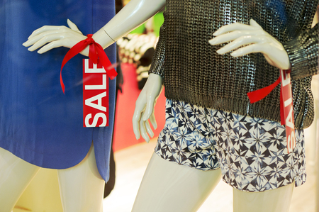 window display: Mannequin in fashion window display with red sale tag Stock Photo