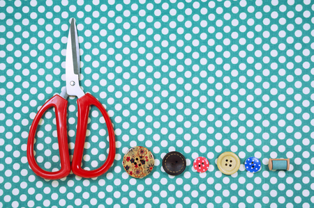 polka dot fabric: Scissors and buttons on blue polka dot fabric background Stock Photo