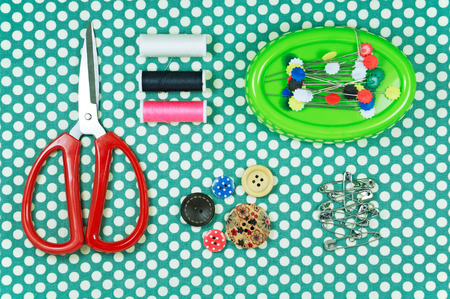polka dot fabric: Sawing kit with red scissors and thread on polka dot fabric background Stock Photo