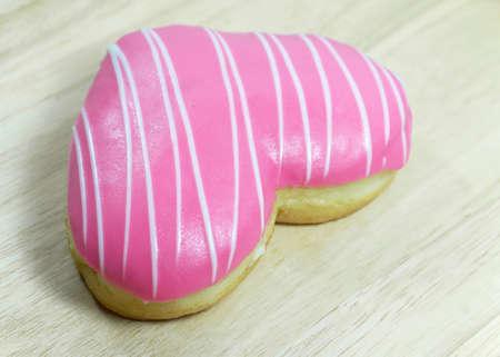 donut shape: Donut in love heart shape on wooden table