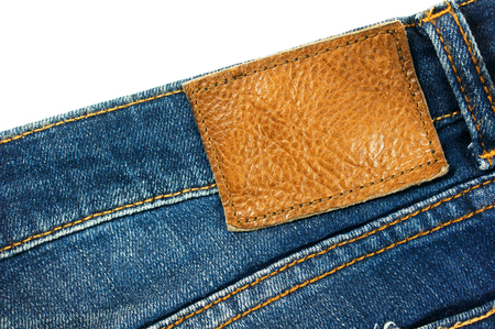 Closeup blue jeans with blank brown leather label isolated on white background photo