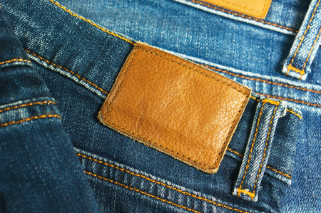 leather label: Jeans with blank brown leather label closeup