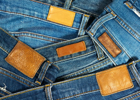 Jeans with brown leather labels texture and background photo
