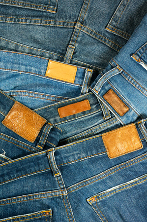 Pile of blue jeans with leather label background photo