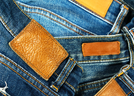 Brown grungy leather label on jeans with pile of jeans photo