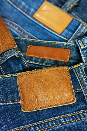 Pile of blue jeans with brown leather label photo