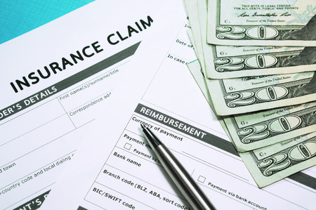 Insurance concept with insurance claim form and money Foto de archivo