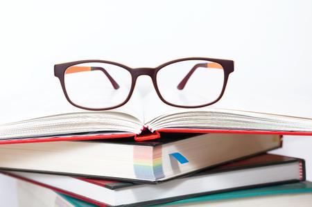 Eyeglasses on stack of books photo