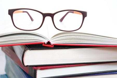 Eyeglasses on book stacks photo