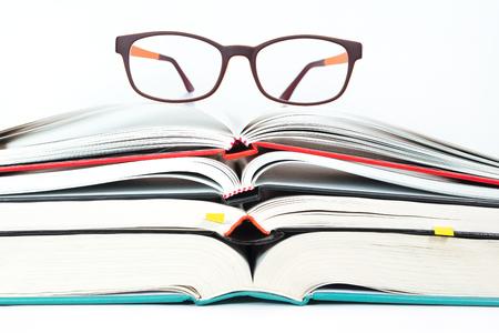 Eyeglasses on stack of open books photo