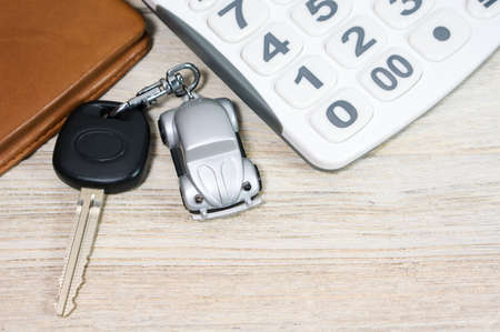 Car key with calculator and wallet on wood table photo