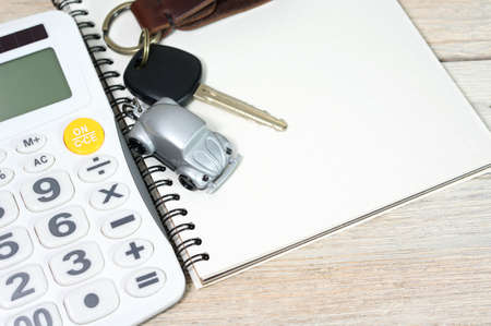 rent: Car toy with car key and calculator on blank notebook