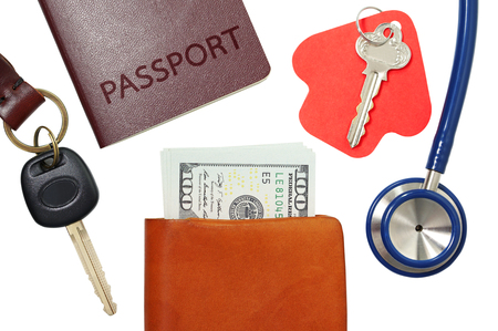 Car key, house key, passport and stethoscope with money in wallet isolated on white background photo