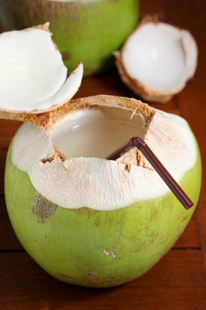 Green coconut water drink with straw on wooden table