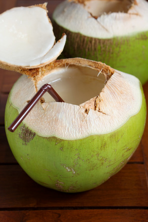Green coconut water drink on wooden table