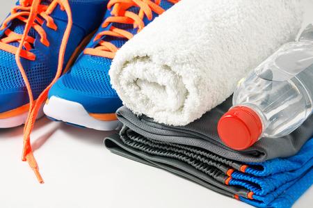 полотенце: Тренажерный зал аксессуары с спортивной одежды полотенце питьевой водой и кроссовки Фото со стока