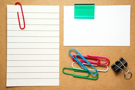 paperclips: Business card with paperclips and note paper on brown cardboard