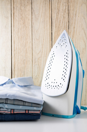Steam iron and shirts on table with wooden background