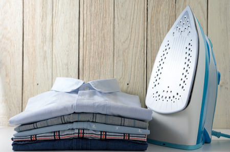 Ironing clothes with shirts and iron with wood background
