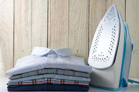 Strijken van kleding met overhemden en ijzer met houten achtergrond Stockfoto