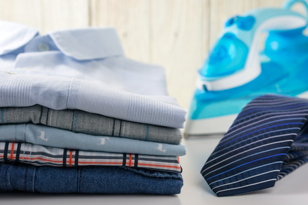 laundry concept: Stack of shirts and tie with iron